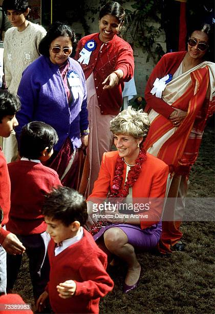 The Princess of Wales talking to children at the Marie Stopes centre in Agra, India, 11th February 1992. Diana is wearing a suit by Catherine Walker.