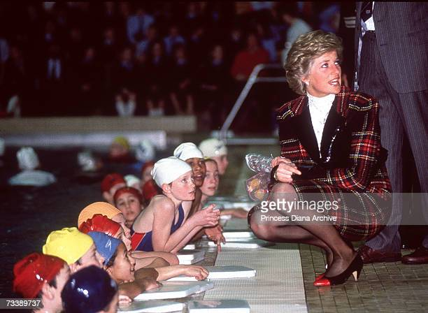 The Princess of Wales visits the Crown Pool Swimming Complex in Ipswich where she crouches down to talk to some children February 1990 She is wearing...