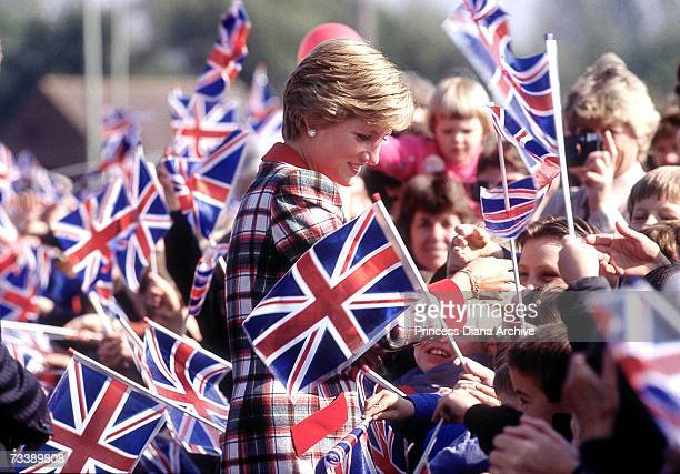The Princess of Wales walks amongst crowds of children waving flags during her visit to Cullompton in Devon September 1990 She is wearing a Catherine...