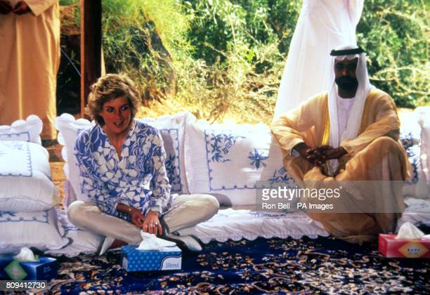 The Princess of Wales wearing a cool blue and white tunic with white silk jodhpur trousers sits with the leading sheikh for the desert picnic at the...