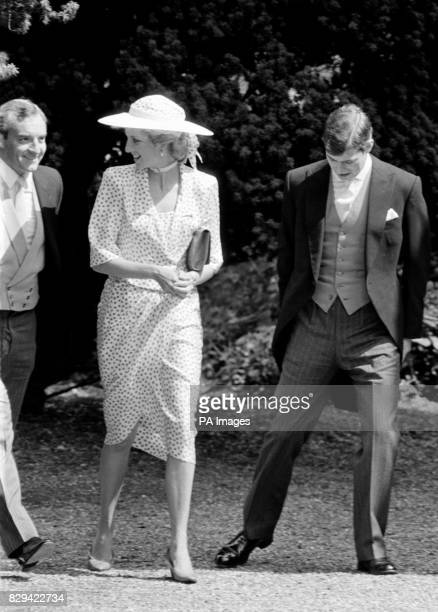 The Princess of Wales wearing a pink spotted silk suit and brimmed white hat smiles at her police bodyguard Barry Mannakee as she arrives at...