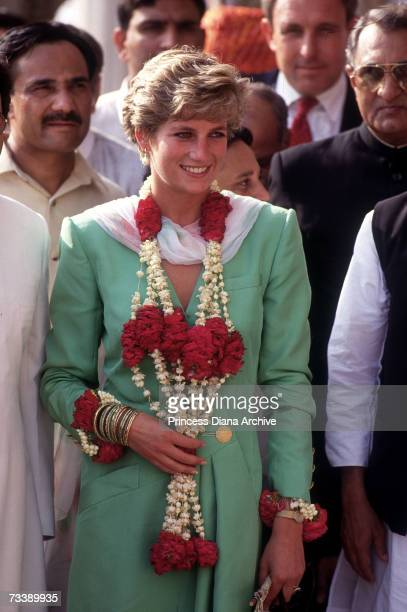 The Princess of Wales wears a floral garland presented to her during a visit to the Shish Mahal fort in Lahore September 1991 Her green coatdress is...