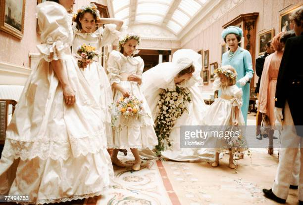 The Princess of Wales with HM The Queen and her bridesmaids behind the scenes at Buckingham Palace on 29th July 1981. Diana is comforting Miss...