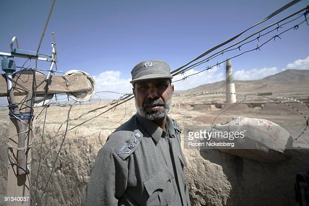The prison warden at the Ghazni provincial jail shows a visiting team of US and Polish army officers his jail's perimeter wall during a security...