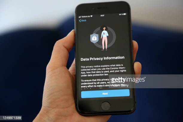 The privacy information screen of the English version of the German federal health ministry's Corona-Warn-App software is seen on an Apple iPhone in...
