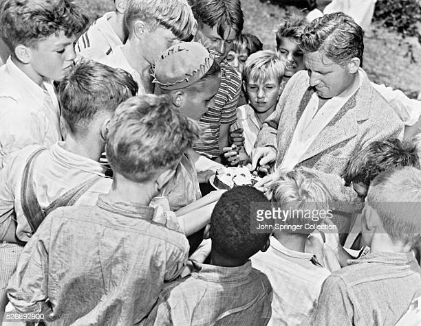 The problem facing actor Spencer Tracy is how to divide four small cup cakes evenly between this group of hungry boys at Boys Town during Tracy's...