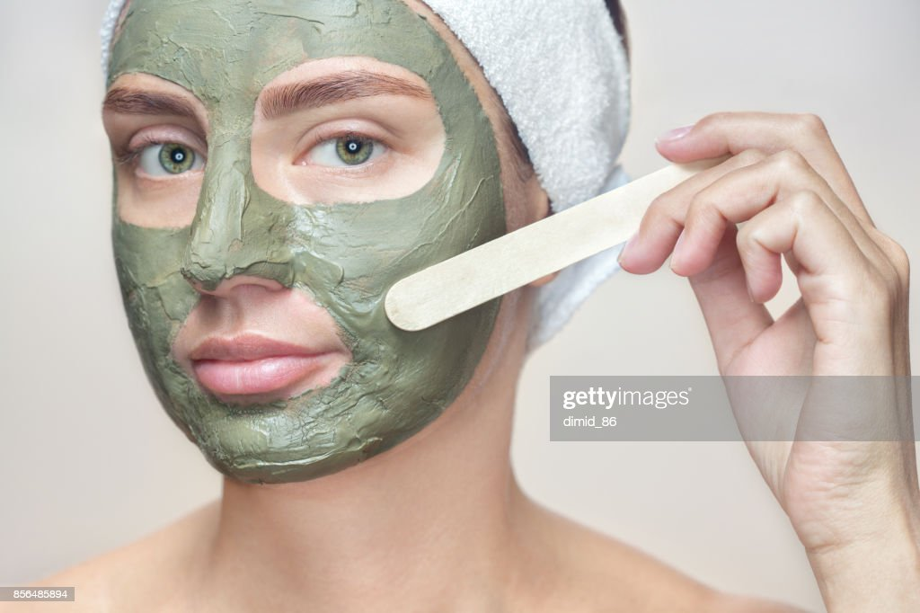 The procedure for applying a mask from clay to the face of a beautiful woman. : Stock Photo