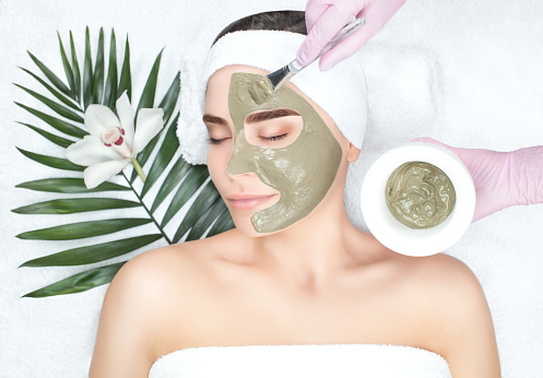 The procedure for applying a mask from clay to the face of a beautiful woman 921945386
