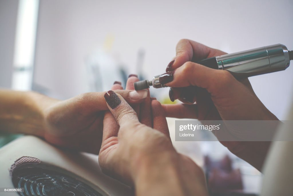The process of manicure at a beauty salon with electrical  file.  Close up. : Stock Photo