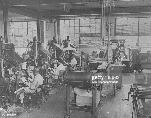 The production and print room of the Afro American newspaper men working at typesetting machines and large machines with rolls of paper 1948