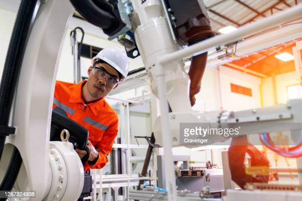 the professional officer check the robot moving  on the jig base on manufacturing factory.. this post for teaching and check quality for right position. - manufacturing stock pictures, royalty-free photos & images