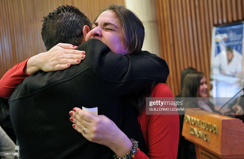 The Programmatic Reintegration Director of the Colombian Agency for Reintegration (ACR), Gisella De Andreis (R), hugs a former member of an illegal armed group during a ceremony in Bogota, on December 11, 2012. The ACR certified on Tuesday a group of 59 people - former members of the illegal armed groups Revolutionary Armed Forces of Colombia (FARC) and United Self-Defense Forces of Colombia (AUC) - who completed their reintegration to society. AFP PHOTO/Guillermo Legaria