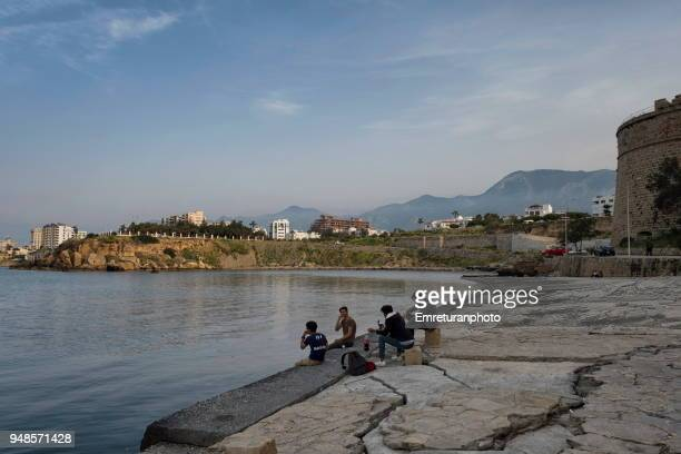 the promenade with people sitting and relaxing in front of girne castle. - emreturanphoto stock pictures, royalty-free photos & images