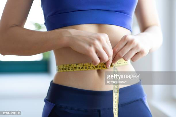 the proof is in the inches - flat stomach stock pictures, royalty-free photos & images