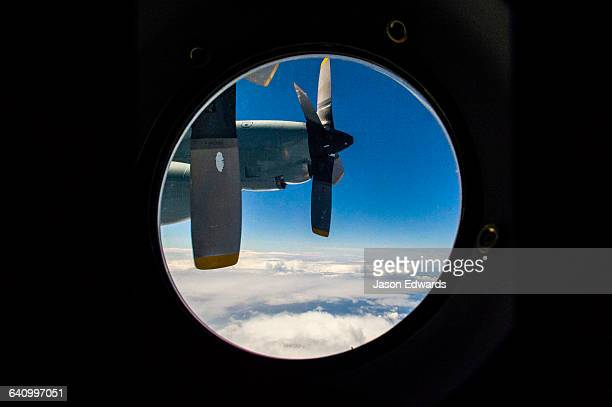 The propeller of a US Air force Hercules through a porthole window flying above the clouds.