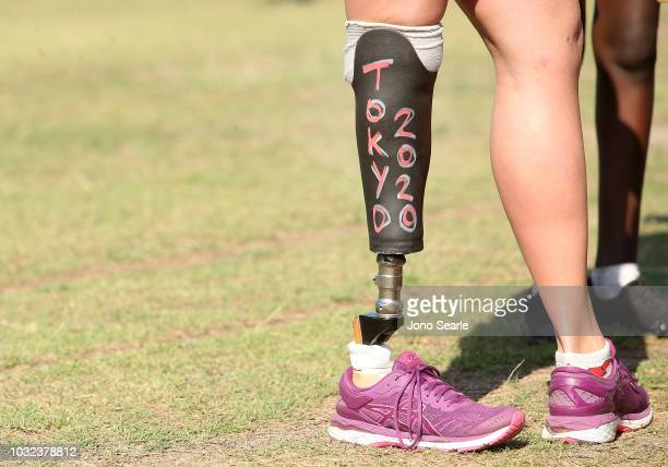 The prosthetic leg of Australian Paralympic swimmer Monique Murphy can be seen featuring the words 'Tokyo 2020' as she talks with students during the...