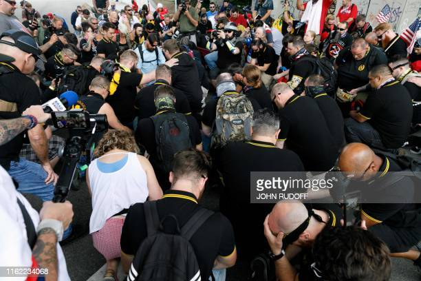 The Proud Boys group stage a moment of prayer before marching across the Morrison Bridge during The End Domestic Terrorism rally at Tom McCall...