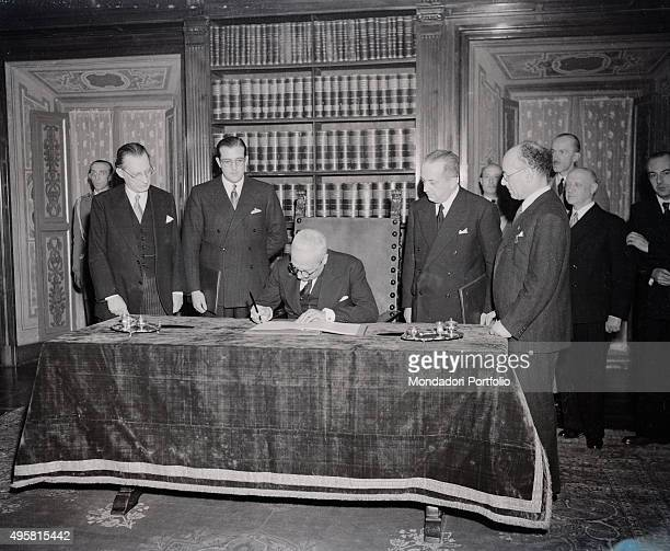 The provisional Head of State of Italy Enrico De Nicola signing the Constitution of the Italian Republic in the presence of the President of the...