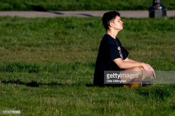 The public seen taking their one period of daily exercise permitted during the coronavirus lockdown at Primrose Hill on March 25, 2020 in London,...