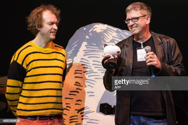 The publisher of US cartoonist Peter Blegvad author of Le Livre de Leviathan and US Derf Backderf author of Mon Ami Dahmer stand on the stage after...