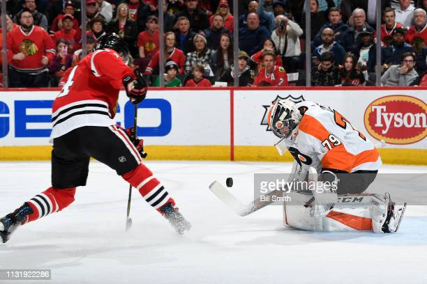 The puck approaches goalie Carter Hart of the Philadelphia Flyers in the first period against the Chicago Blackhawks at the United Center on March 21...