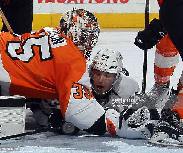 The puck bounces in front of Dustin Brown of the Los Angeles Kings as he is held by goaltender Steve Mason of the Philadelphia Flyers during overtime...