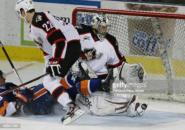 The puck bounces off of Portland Pirates' goalie Mark Visentin as Phil Lane gets tangled with Bridgeport Sound Tigers' Brock Nelson during their game...