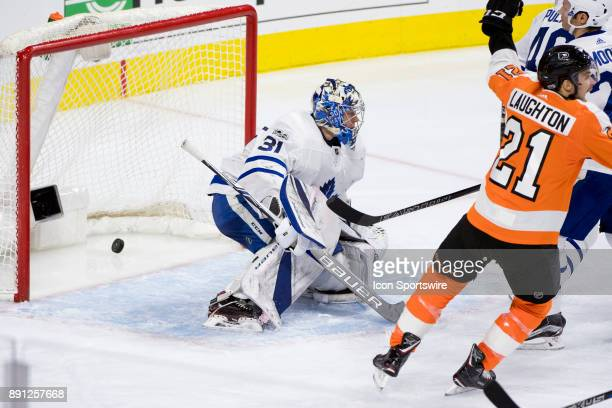 The puck falls into the net over Toronto Maple Leafs Goalie Frederik Andersen while Philadelphia Flyers Center Scott Laughton turns to celebrate in...