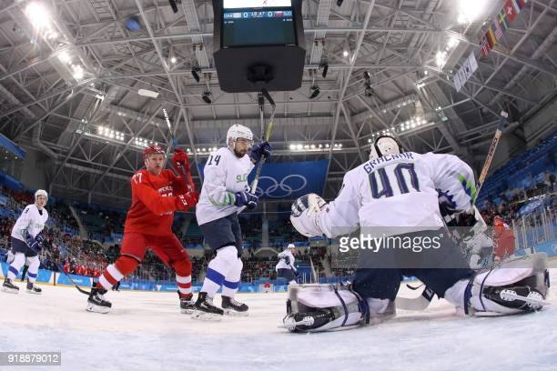 The puck flies in the air past Russia's Kirill Kaprizov and Slovenia's Matic Podlipnik in the men's preliminary round ice hockey match between the...