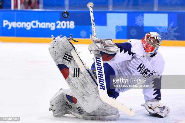TOPSHOT The puck flies past South Korea's Matt Dalton in the men's preliminary round ice hockey match between Canada and South Korea during the...