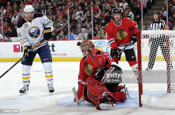 The puck flies toward goalie Marty Turco of the Chicago Blackhawks as teammate Brent Seabrook and Steve Sullivan of the Buffalo Sabres watch from...