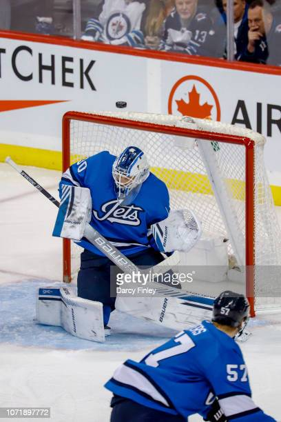 The puck flies up the in air above goaltender Laurent Brossoit of the Winnipeg Jets during second period action against the Chicago Blackhawks at the...