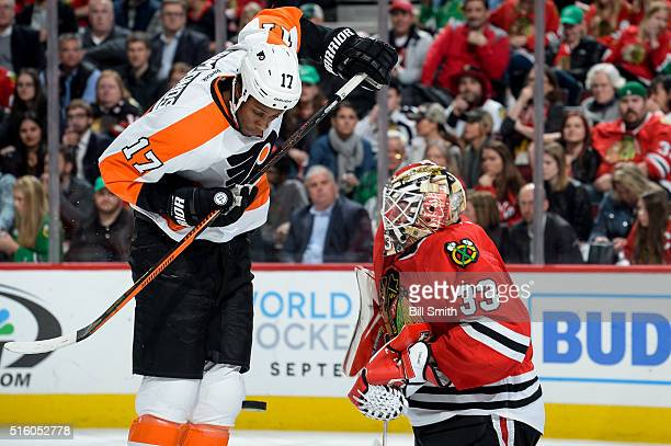 The puck flys toward goalie Scott Darling of the Chicago Blackhawks past Wayne Simmonds of the Philadelphia Flyers in the second period of the NHL...