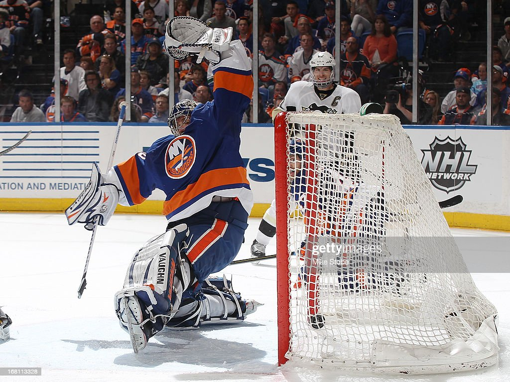 The puck gets past Evgeni Nabokov #20 of the New York Islanders on a shot by Chris Kunitz #14 of the Pittsburgh Penguins for the game winning goal in Game Three of the Eastern Conference Quarterfinals during the 2013 NHL Stanley Cup Playoffs at Nassau Veterans Memorial Coliseum on May 5, 2013 in Uniondale, New York. The Penguins defeated the Islanders 5-4 in overtime.