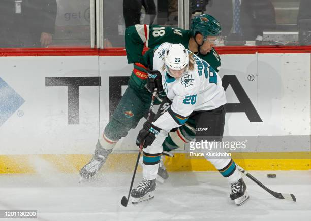 The puck gets past Marcus Sorensen of the San Jose Sharks and Jordan Greenway of the Minnesota Wild during the second period of the game on February...