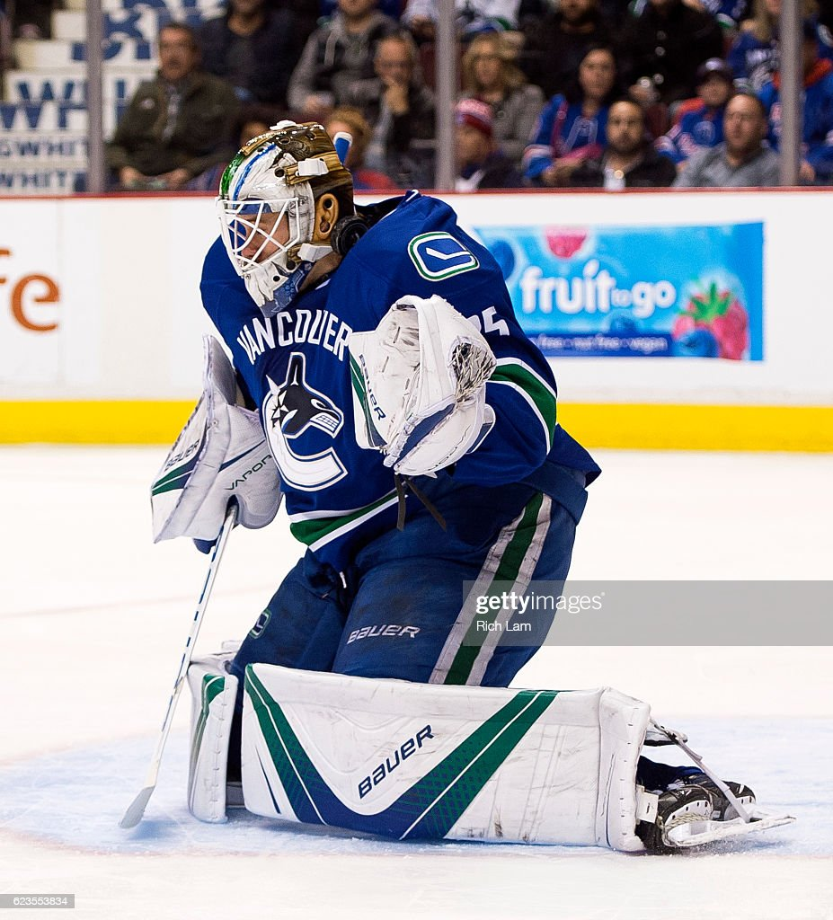The puck hits goalie Jacob Markstrom #25 of the Vancouver Canucks in the neck while making a save against the New York Rangers during the third period in NHL action on November 15, 2016 at Rogers Arena in Vancouver, British Columbia, Canada.