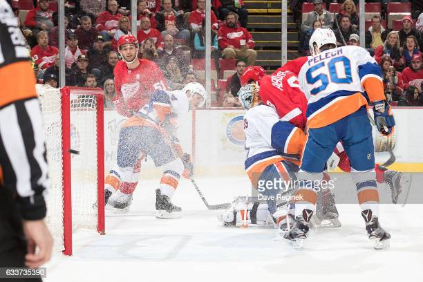 The puck is shot wide of goaltender Thomas Greiss of the New York Islanders as he is ran into by Justin Abdelkader of the Detroit Red Wings during an...