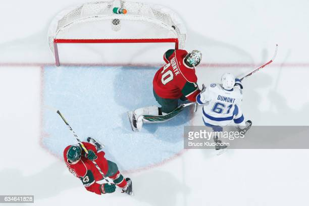 The puck lands on the back of the net as Gustav Olofsson and goalie Devan Dubnyk of the Minnesota Wild defend their goal against Gabriel Dumont of...