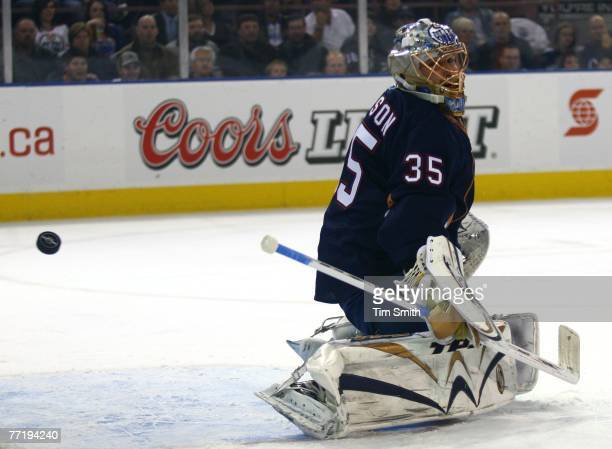 The puck sails past goalie Dwayne Roloson of the Edmonton Oilers but hits the post during the first period of the Oilers home opener against the San...