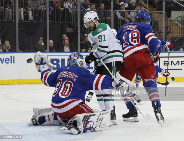 The puck sails past Henrik Lundqvist of the New York Rangers as he is screened by Tyler Seguin of the Dallas Stars during the first period at Madison...