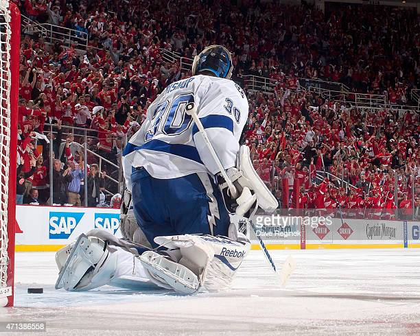 The puck sits behind goalie Ben Bishop of the Tampa Bay Lightning as the Detroit Red Wings bench and hometown fans erupt after teammate Tomas Tatar...