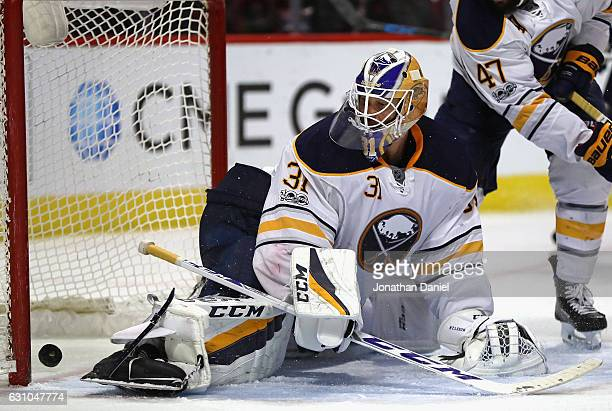 The puck slips past Anders Nilsson of the Buffalo Sabres on a third period goal by Artem Anisimov of the Chicago Blackhawks at the United Center on...