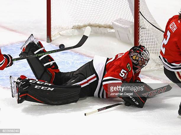 The pucks slips past Corey Crawford of the Chicago Blackhawks on a goal by Jay Beagle the Washington Capitals at the United Center on November 11...
