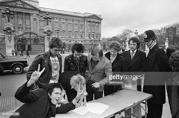 The punk rock group, The Sex Pistols, are about to be moved by a policeman as they sign a copy of their new recording contract with A & M Records...