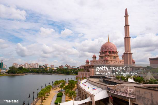the putra mosque or pink mosque is the principal mosque of putrajaya wilaya, malaysia. located next to the perdana putra, which houses the malaysian prime minister's office and man-made putrajaya lake. - jerusalem stock-fotos und bilder