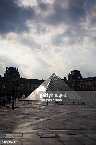 The Pyramide du Louvre in the courtyard of the Louvre museum is illuminated by a sunbeam on September 6 2013 in Paris France