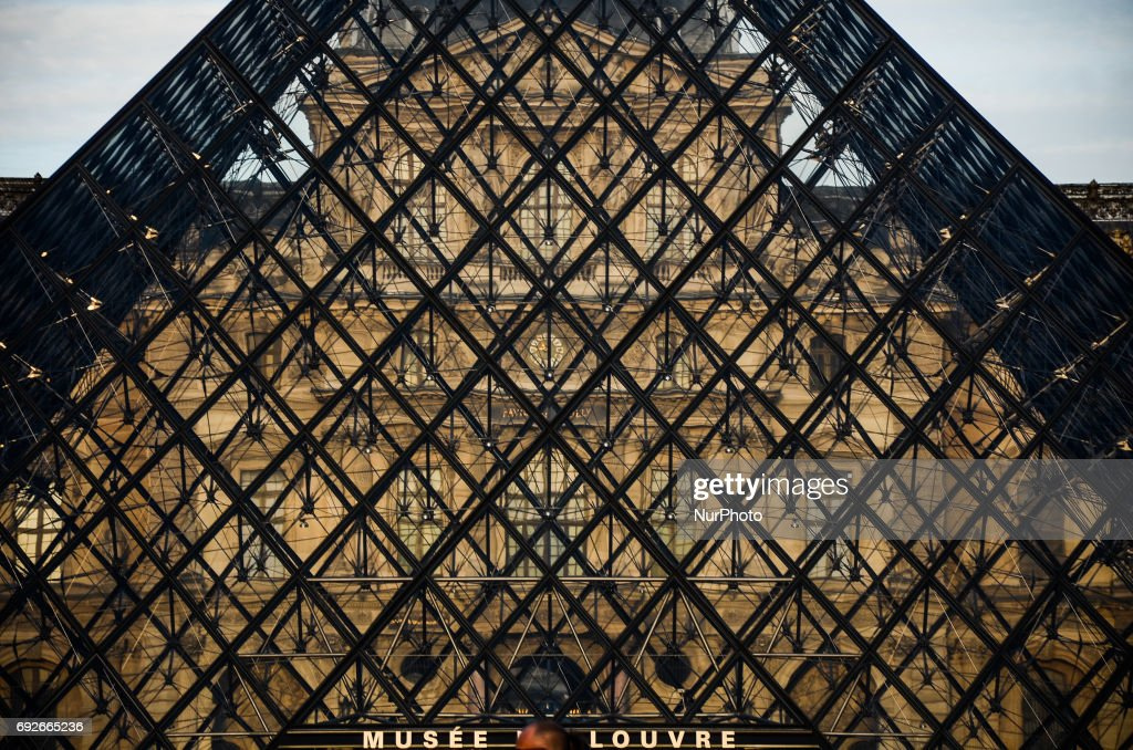 The pyramide of the Louvre museum on sunset. People used the first days of the summer for walking around the French capital of Paris. The temperature of the weather is about 25 celsius degrees Paris, France on June 04, 2017