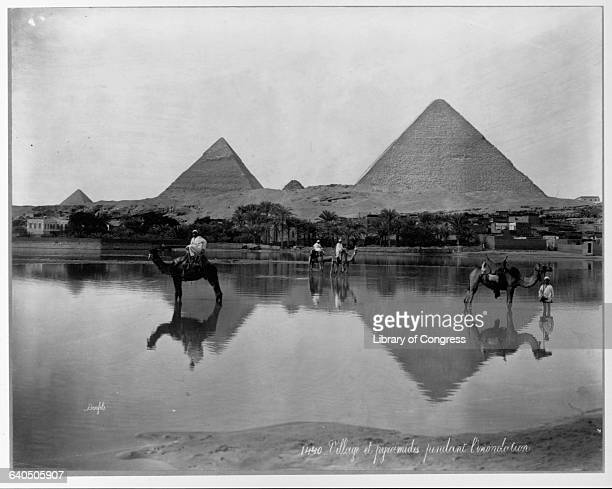 The pyramids at Giza cast their reflections on floodwaters at the edge of the Nile as they have done for centuries