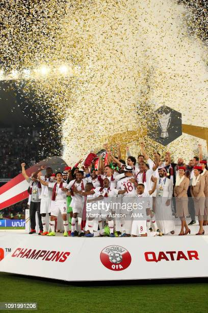 The Qatar players celebrate with the trophy at the end of the AFC Asian Cup final match between Japan and Qatar at Zayed Sports City Stadium on...