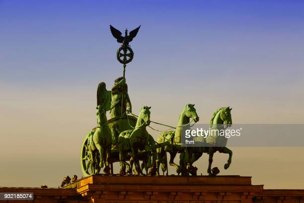 The Quadriga Statue on the Brandenburg Gate in Berlin at sunset (Germany)